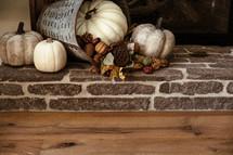 white pumpkins on a fireplace