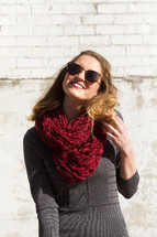 woman smiling outdoors in a scarf and sunglasses
