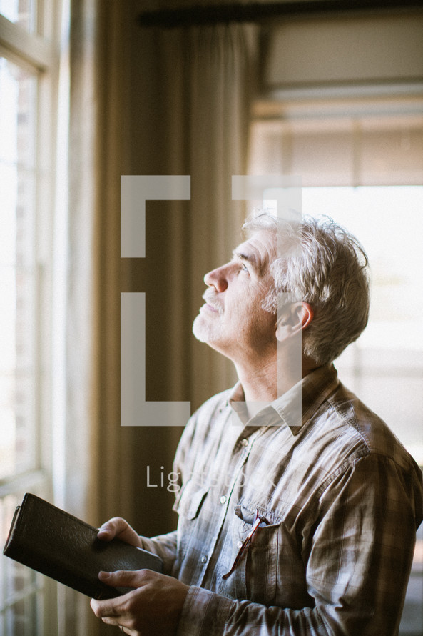 Man gazing our window with Bible in his hands.