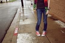 A teenager standing on a sidewalk
