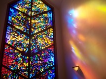 The Window to Heaven - a stained glass window in a small chapel reflects the light and love of Heaven radiating light as a prism on the walls of the church chapel.