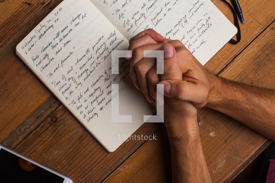 praying hands over a journal