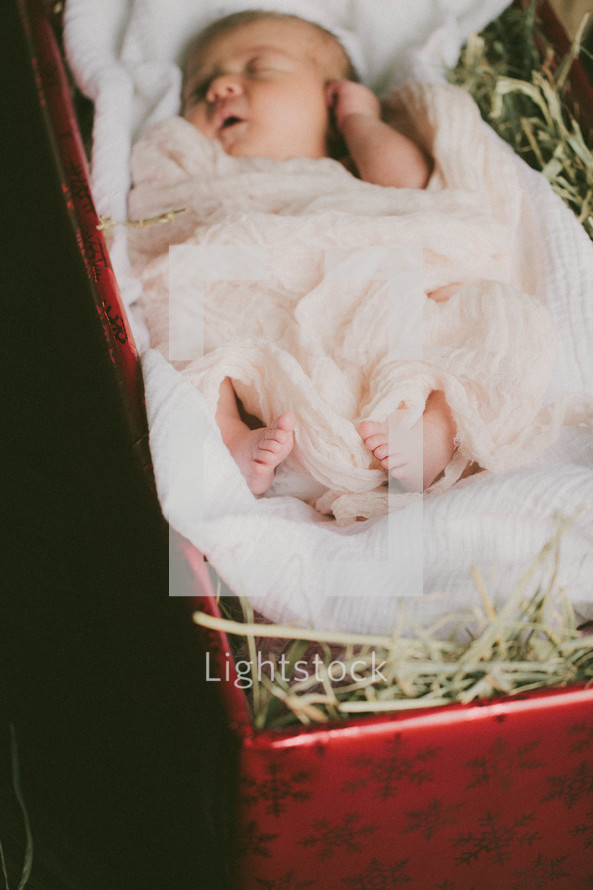 A baby lying in a Christmas present full of hay