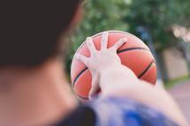 teen boy gripping a basketball