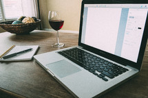 wine glass, laptop, pen, and notepad