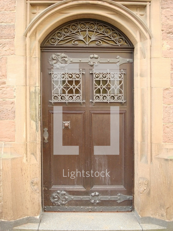 A decorative brown residence door in the middle of a town.
