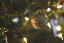 gold glitter ornament on a Christmas tree