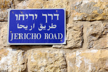 Jericho Road sign in Hebrew, Arabic and English on a stone wall in the Old City of Jerusalem.