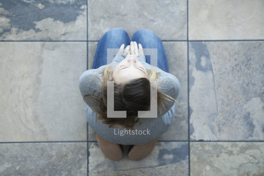 Aerial view of woman sitting on her knees on tiles in prayer.