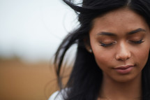 face of a young woman with closed eyes praying