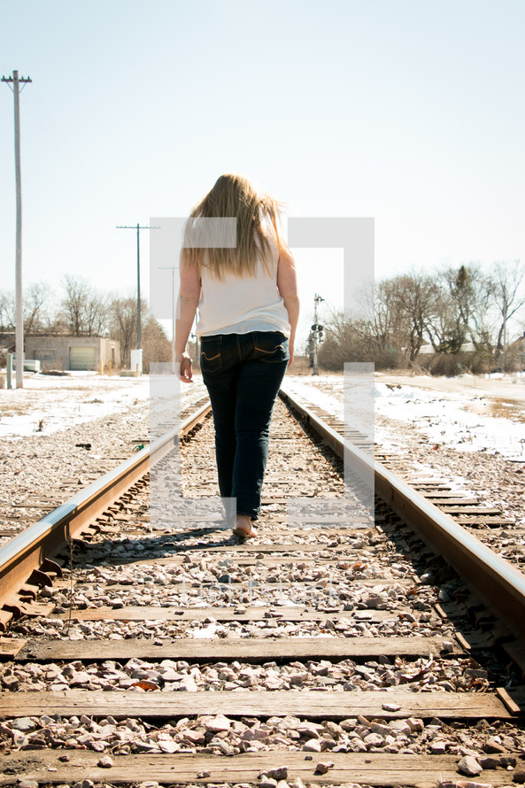 teen girl walking on a train tracks