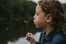 a girl making a wish blowing on a dandelion