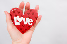 hand holding up a paper heart with the word love