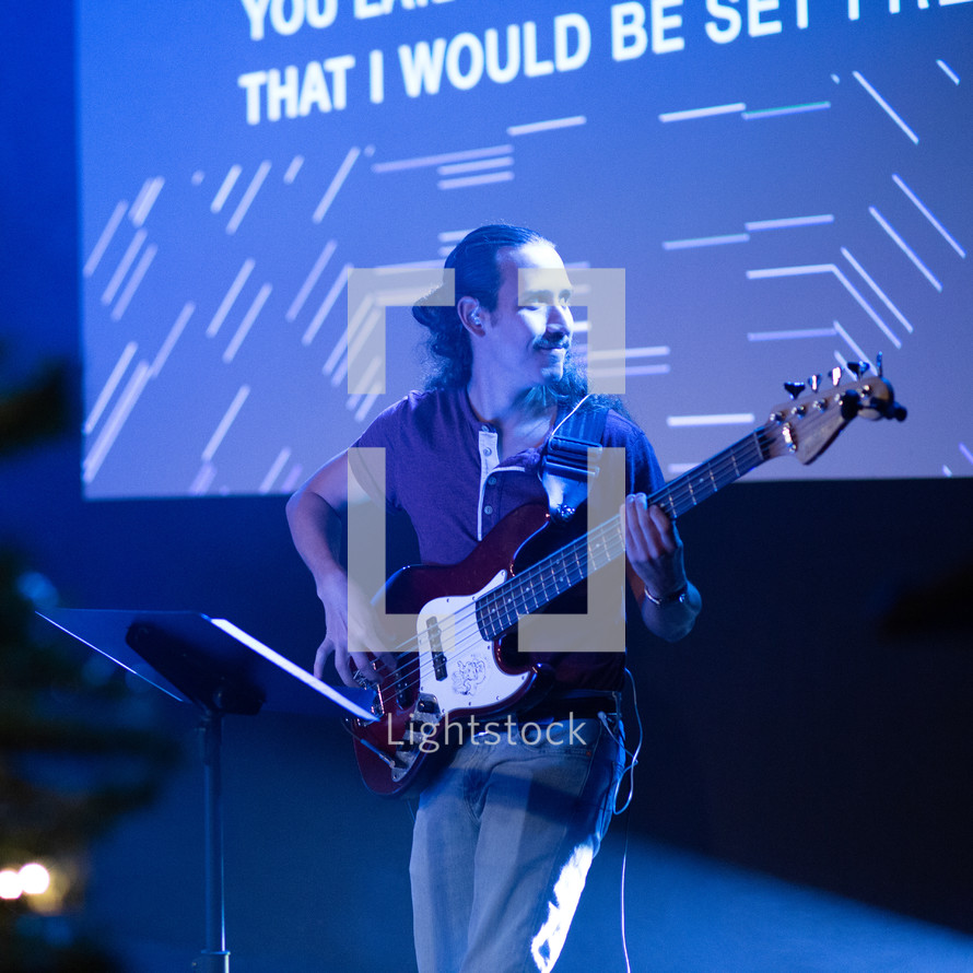 man playing a guitar on stage