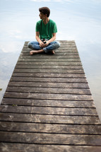 Man sitting at the end of a wooden pier on a lake.