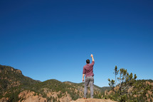 a man standing on a mountain with hand raised