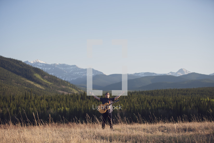 a man with a guitar standing in a field with raised arms and a mountain view
