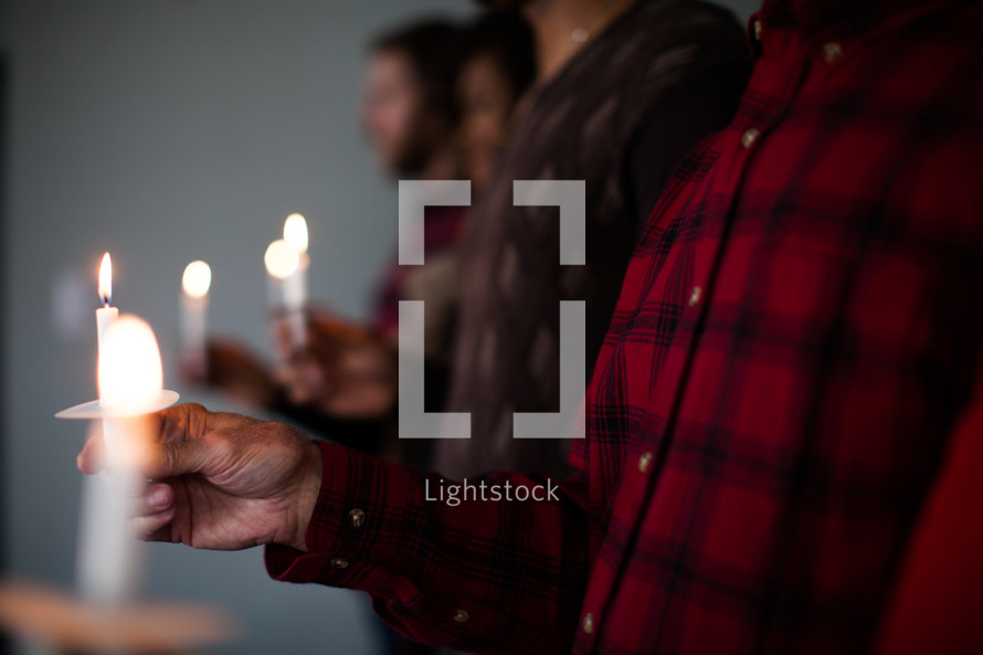 A row of people at a Christmas candlelight service.