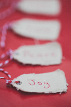 """Christmas gift tags, the first one reading """"Joy"""", on a red background."""