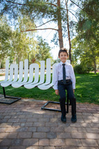 portrait of a boy in dress clothes sitting on a bench in a park