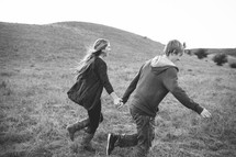a couple holding hands running in a field