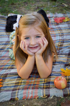 smiling little girl on a plaid blanket