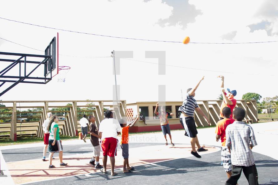 Teens playing basketball outside.