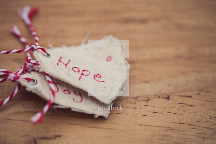 "A stack of Christmas gift tags, the top one reading ""Hope,"" on a wood grain background."