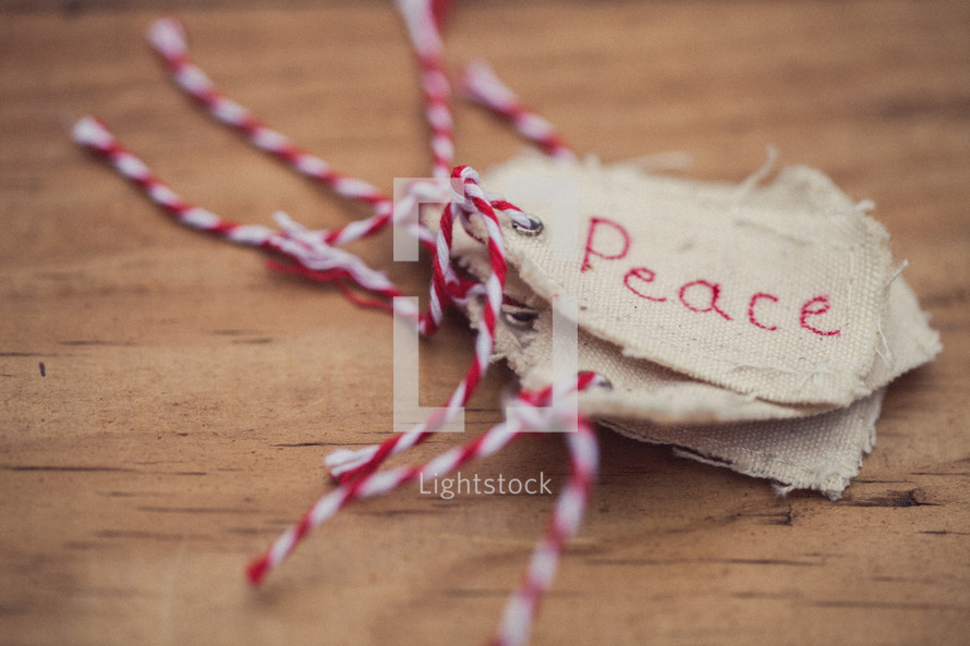 "A stack of Christmas gift tags, the top one reading ""Peace,"" on a wood grain background."