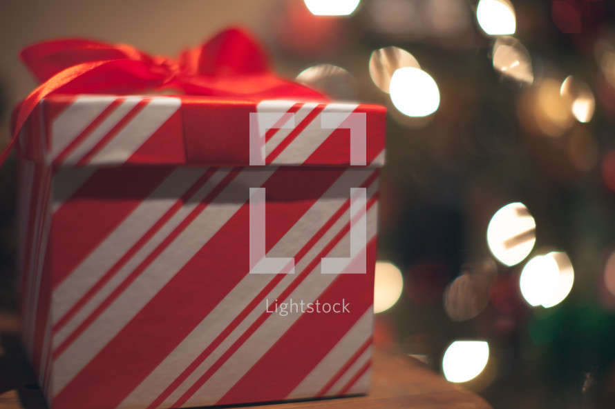 A red and white gift box with a Christmas tree in the background