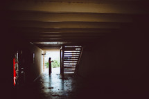 a woman standing at the end of a dark hallway