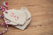 """A stack of Christmas gift tags, the top one labeled """"Joy"""", on a wood table."""