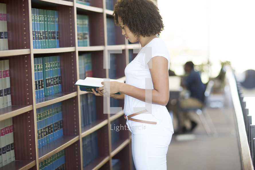 a woman looking at books in a library
