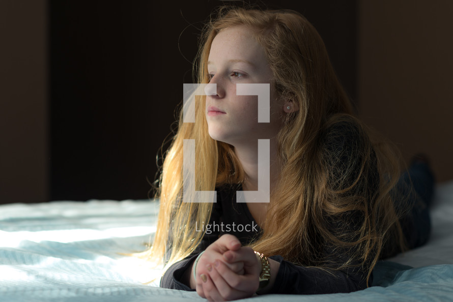 teen girl praying on a bed