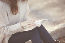woman sitting reading a Bible outside.