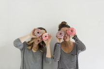 women holding donuts and acting silly