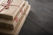 Gifts wrapped in brown paper on a table.