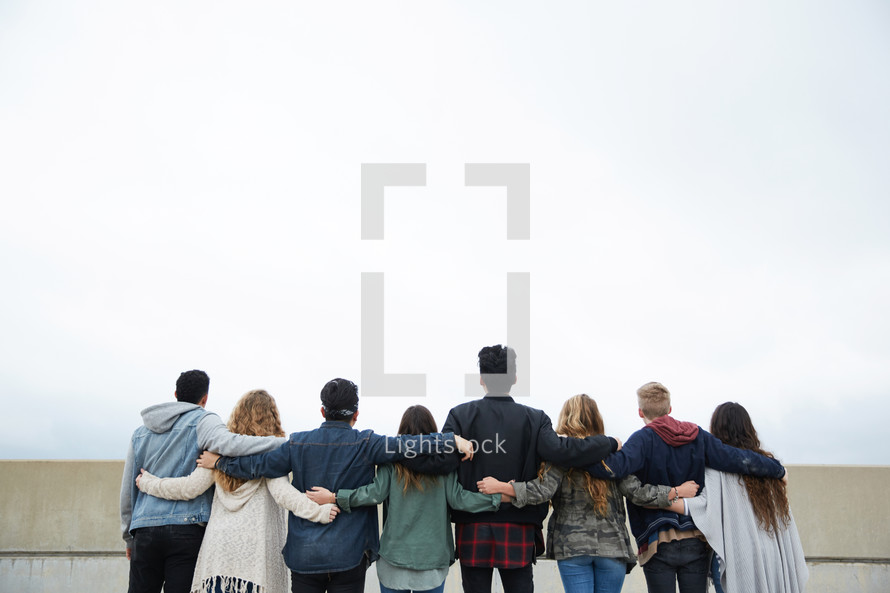 row of teens standing with arms around each other