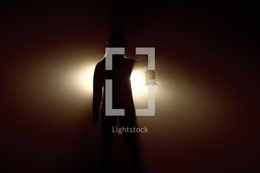 woman holding a lantern lighting the way