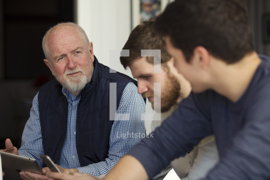 men at a meeting with cellphones and laptops