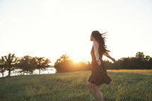a woman dancing by herself in a field.