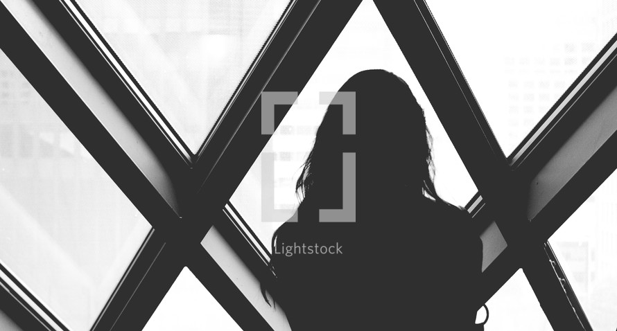 Silhouette of a woman looking out of diamond shaped windows.