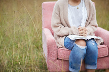 a woman sitting in a chair in a field with praying hands over the pages of a Bible