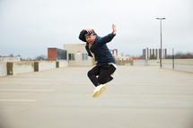 an Asian boy jumping up in a parking deck