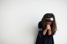 girl with head bowed in prayer
