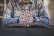 A man with hands folded in prayer on an open Bible