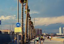 tourists walking on sidewalks near a beach