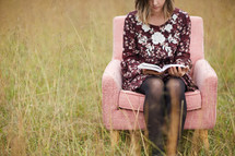 a young woman sitting in a chair in a field reading a Bible