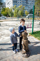 Portrait of brothers hugging a dog statue