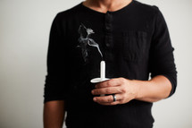a man holding a blown out candle
